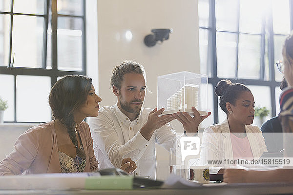 Focused architects examining model in conference room meeting