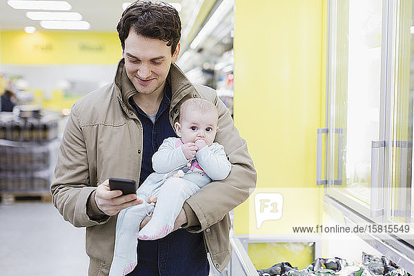 Father with baby daughter checking smart phone  shopping in supermarket Father with baby daughter checking smart phone, shopping in supermarket
