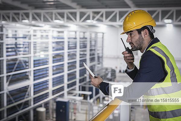 Male supervisor with digital tablet talking  using walkie-talkie n platform in factory