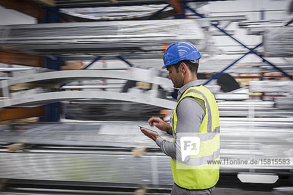 Male worker using digital tablet in steel factory Male worker using digital tablet in steel factory