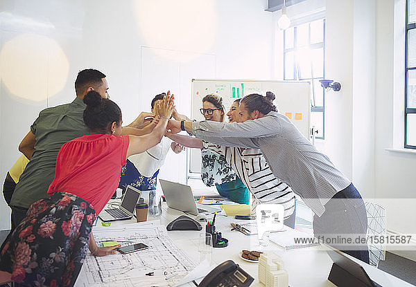 Enthusiastic architects high-fiving in conference room meeting