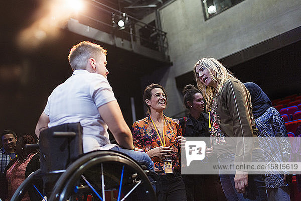 Women in conference audience talking to speaker in wheelchair