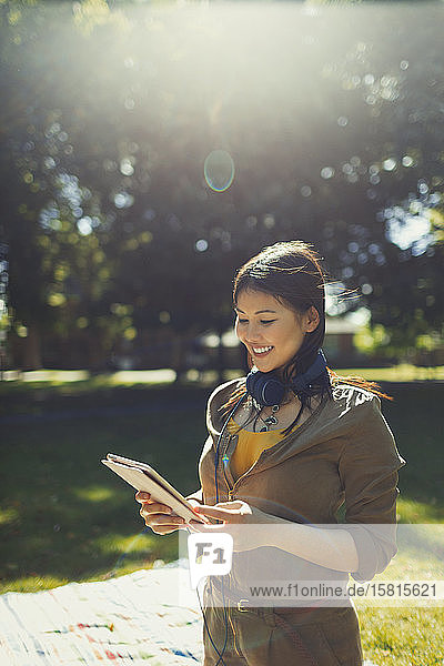 Smiling young woman with headphones using digital tablet in sunny summer park
