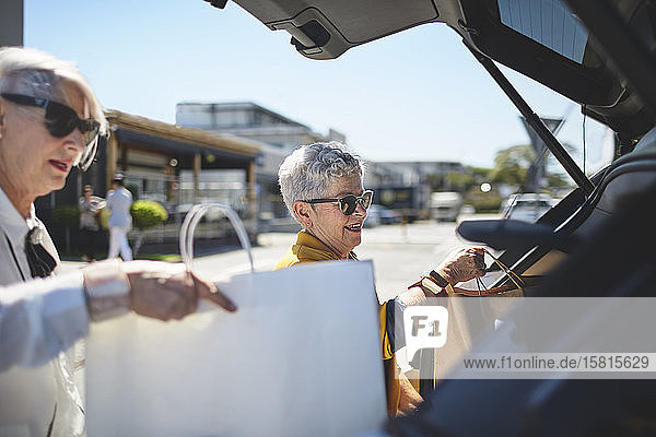 Senior women loading shopping bags into back of car in sunny parking lot