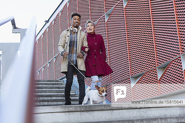 Smiling young couple walking dog down urban  modern stairs