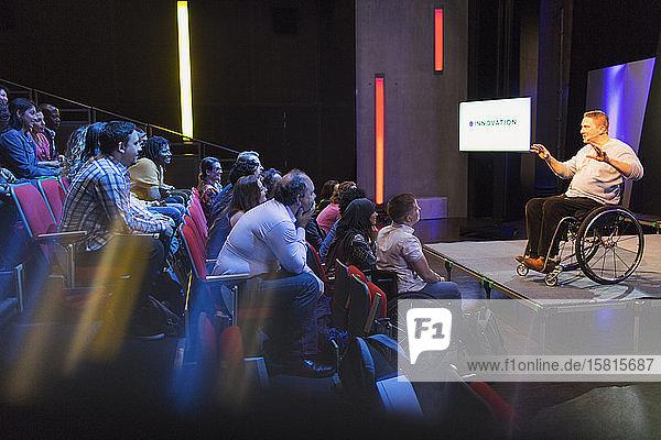 Aufmerksames Publikum hört einer Rednerin im Rollstuhl auf der Bühne zu
