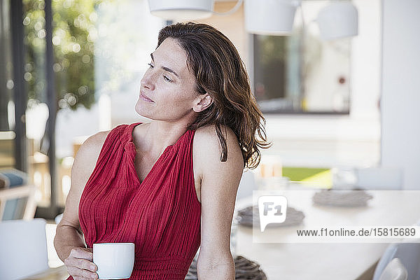 Pensive brunette woman drinking coffee in dining room  looking away