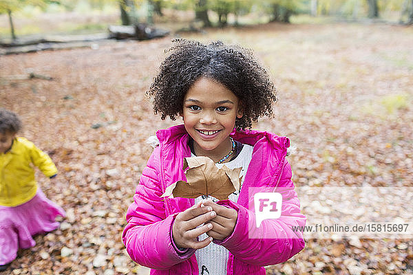 Portrait happy girl holding autumn leaf in woods Portrait happy girl holding autumn leaf in woods