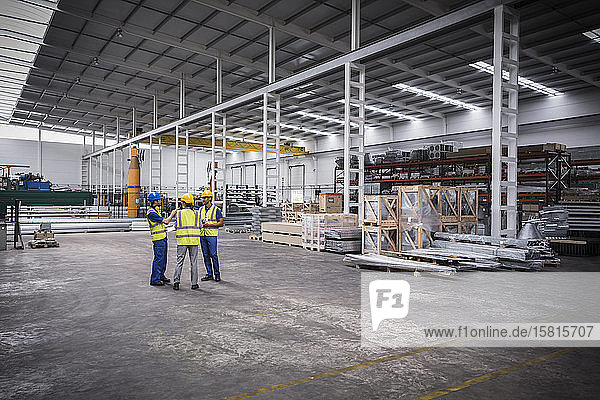 Supervisor and workers talking in warehouse Supervisor and workers talking in warehouse
