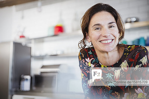 Portrait confident smiling brunette woman in kitchen