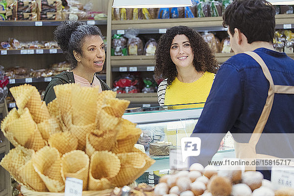 Women talking with worker at bakery display case in supermarket