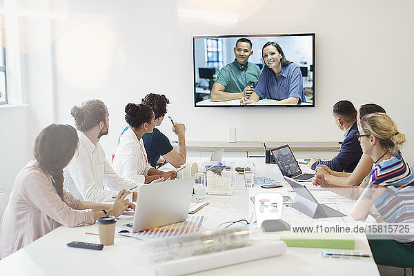 Designers video conferencing with colleagues in conference room meeting