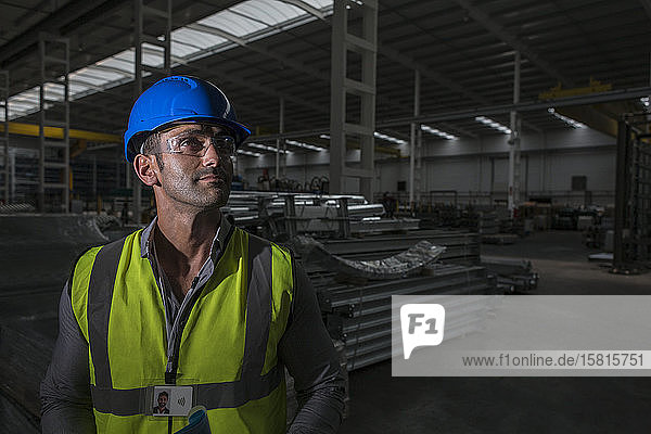 Portrait confident male worker looking away in dark factory