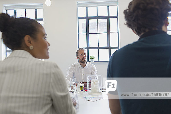 Focused male architect listening in conference room meeting Focused male architect listening in conference room meeting