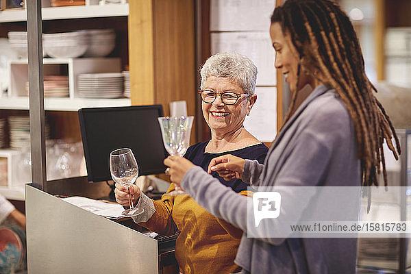 Lächelnder Angestellter hilft Frau beim Einkaufen von Weingläsern