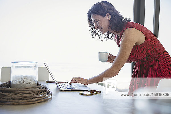 Brunette woman drinking coffee and using laptop on dining table Brunette woman drinking coffee and using laptop on dining table