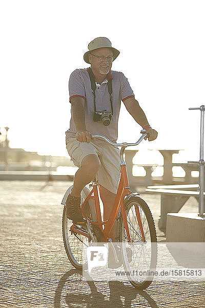 Active senior man tourist bike riding on sunny boardwalk
