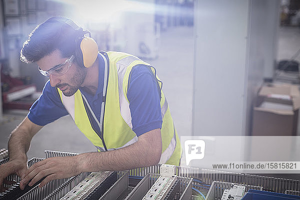 Focused male engineer wearing ear protectors  assembling equipment in factory