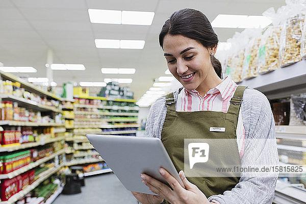 Smiling female grocer using digital tablet in supermarket aisle Smiling female grocer using digital tablet in supermarket aisle
