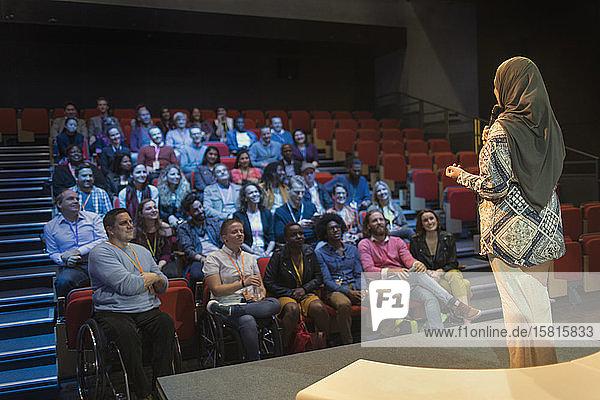 Publikum hört einer Rednerin im Hijab zu  die auf der Bühne spricht
