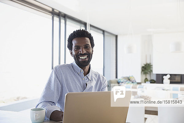 Portrait smiling  enthusiastic businessman drinking coffee  working at laptop in kitchen Portrait smiling, enthusiastic businessman drinking coffee, working at laptop in kitchen