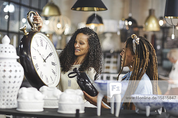 Women shopping for wall clocks in home decor shop