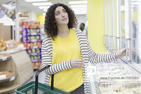 Woman shopping frozen food in supermarket