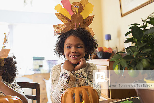 Portrait happy girl with turkey hat carving pumpkin at table