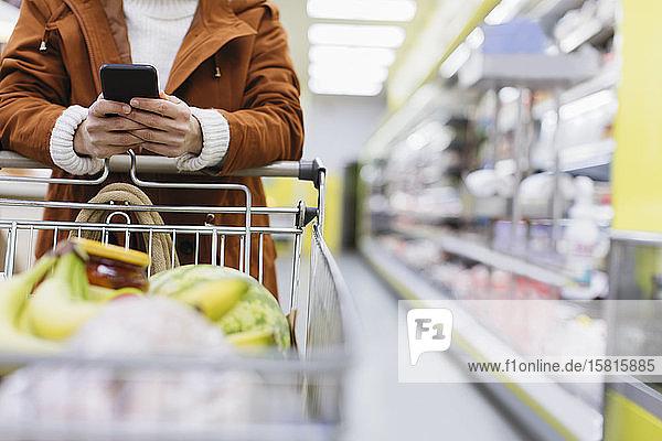 Woman with smart phone pushing shopping cart in supermarket Woman with smart phone pushing shopping cart in supermarket