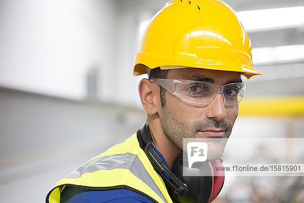 Portrait serious male worker in protective eyewear and hard-hat in factory Portrait serious male worker in protective eyewear and hard-hat in factory