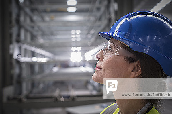 Profile pensive female worker looking up in factory