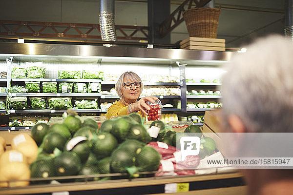 Ältere Frau beim Einkaufen von Tomaten in der Gemüseabteilung eines Supermarkts