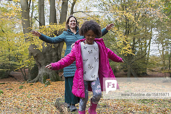 Mother and daughter balancing on fallen log in autumn woods