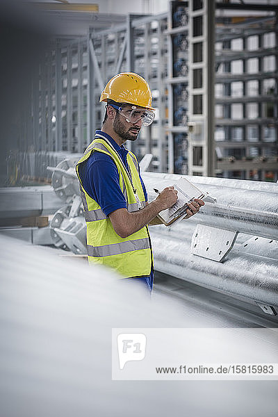 Male worker with clipboard working in steel factory Male worker with clipboard working in steel factory