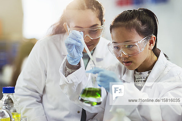 Girl students conducting chemistry experiment in classroom laboratory