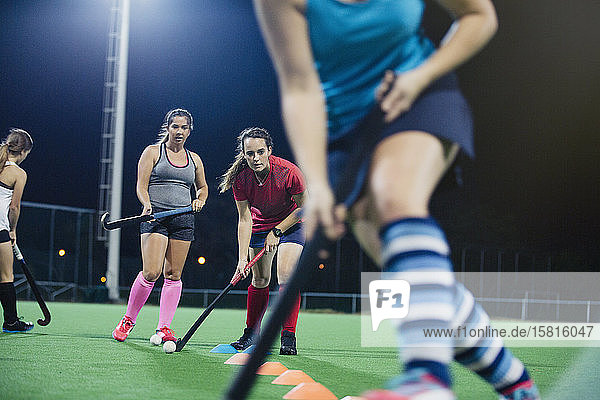 Young female field hockey players practicing sports drill on field Young female field hockey players practicing sports drill on field