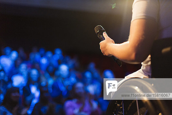 Female speaker in wheelchair holding microphone on stage