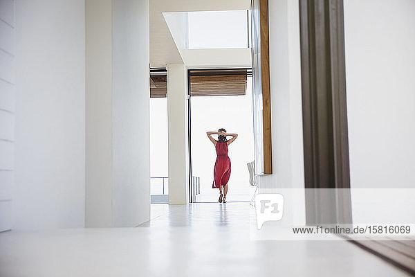 Woman standing with hands behind head in home corridor