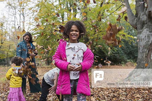 Portrait happy girl playing with family in autumn leaves