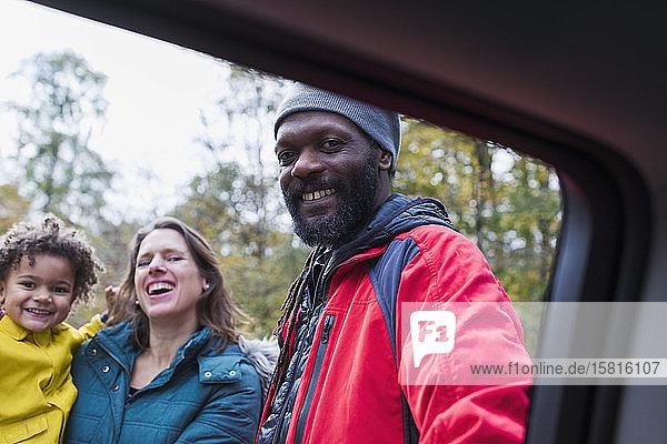Portrait happy multiethnic family outside car Portrait happy multiethnic family outside car