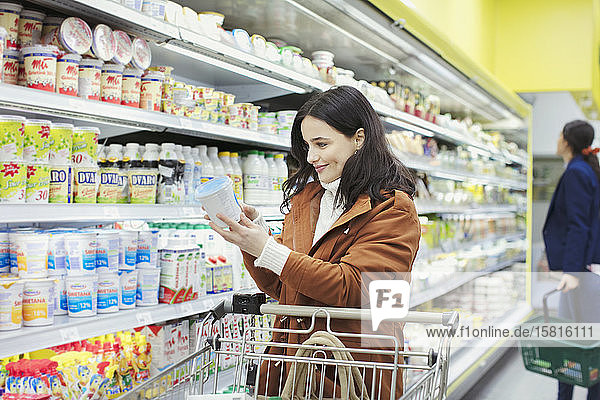 Smiling woman reading label on container in supermarket