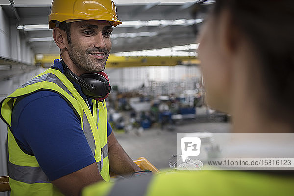 Smiling male supervisor talking to coworker on platform in factory
