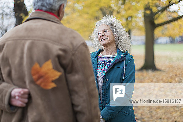 Playful senior husband surprising wife with autumn leaf in park