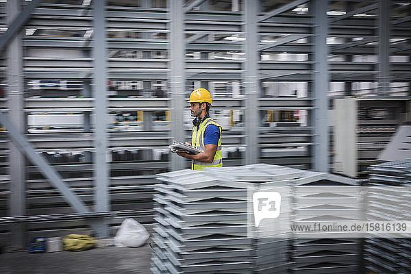 Male worker with clipboard walking in steel factory Male worker with clipboard walking in steel factory