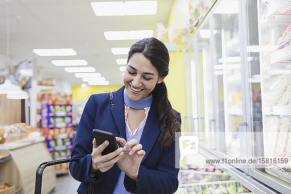 Smiling woman with smart phone shopping in supermarket Smiling woman with smart phone shopping in supermarket