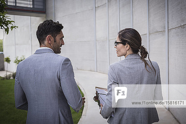 Businessman and businesswoman walking and talking on sidewalk