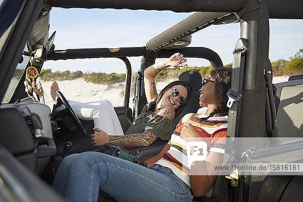 Playful young women friends relaxing  enjoying road trip in jeep