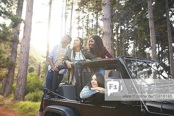 Young friends in jeep looking up at trees in woods  enjoying road trip Young friends in jeep looking up at trees in woods, enjoying road trip