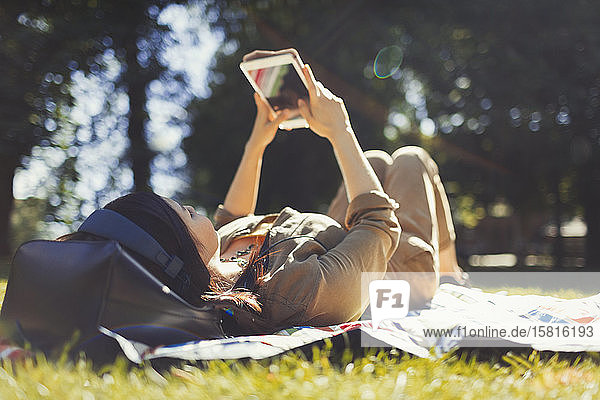 Young woman using digital tablet in sunny summer park