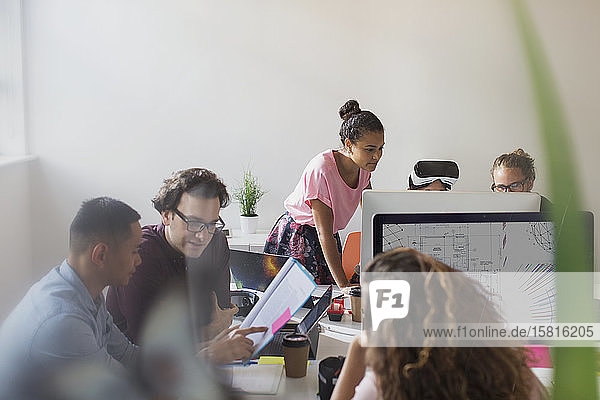 Computer programmers and designers working in open plan office